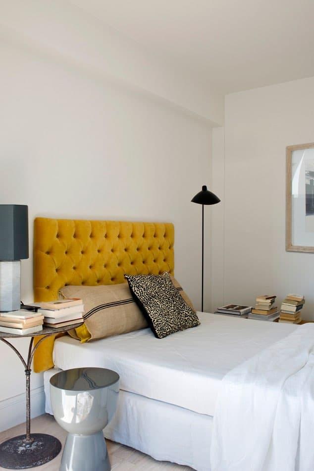 Estudio María Santos Reforma integral y decoración de vivienda minimalista Madrid dormitorio cabecero amarillo terciopelo capitoné