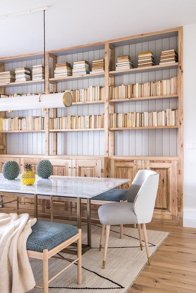 Estudio María Santos Reforma integral y decoración de vivienda minimalista Madrid silla blanca biblioteca tonos madera comedor