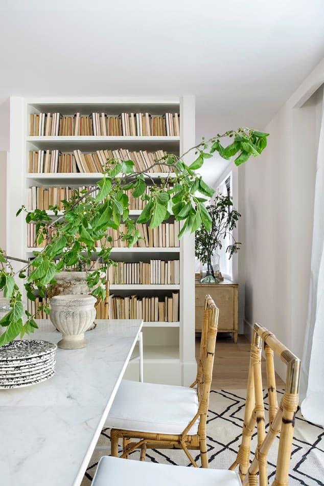 Estudio María Santos Reforma integral y decoración de vivienda minimalista Madrid comedor en tonos blancos con sillas de mimbre y biblioteca