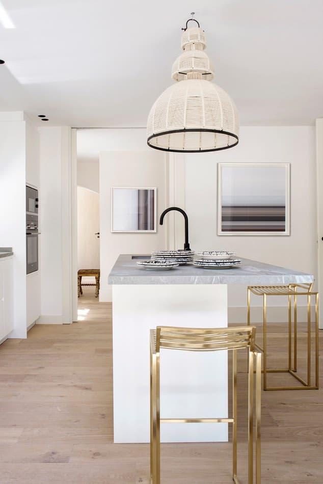 Estudio María Santos Reforma integral y decoración de vivienda minimalista Madrid encimera de mármol blanco cocina y taburetes dorados