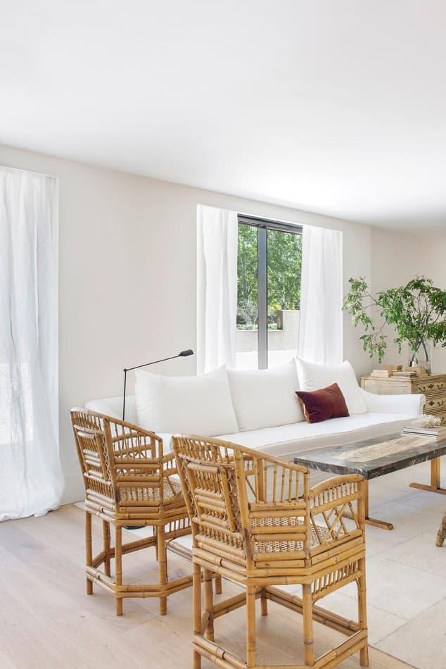 Estudio María Santos Reforma integral y decoración de vivienda minimalista Madrid salon con sofa blanco y cojin de terciopelo burdeos y sillas en mimbre