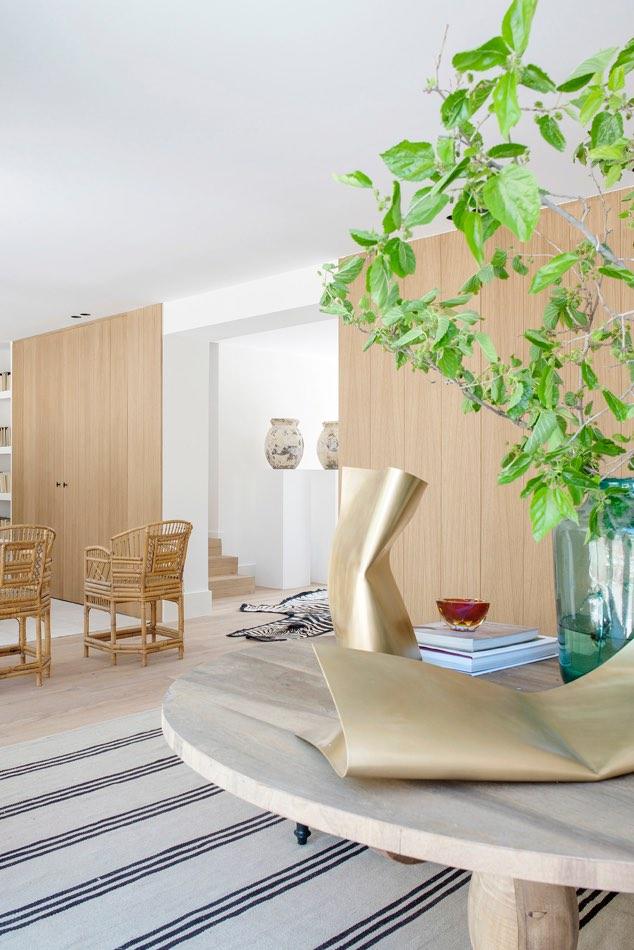 Estudio María Santos Reforma integral y decoración de vivienda minimalista Madrid alfombra rayas azules y figura moderna dorada