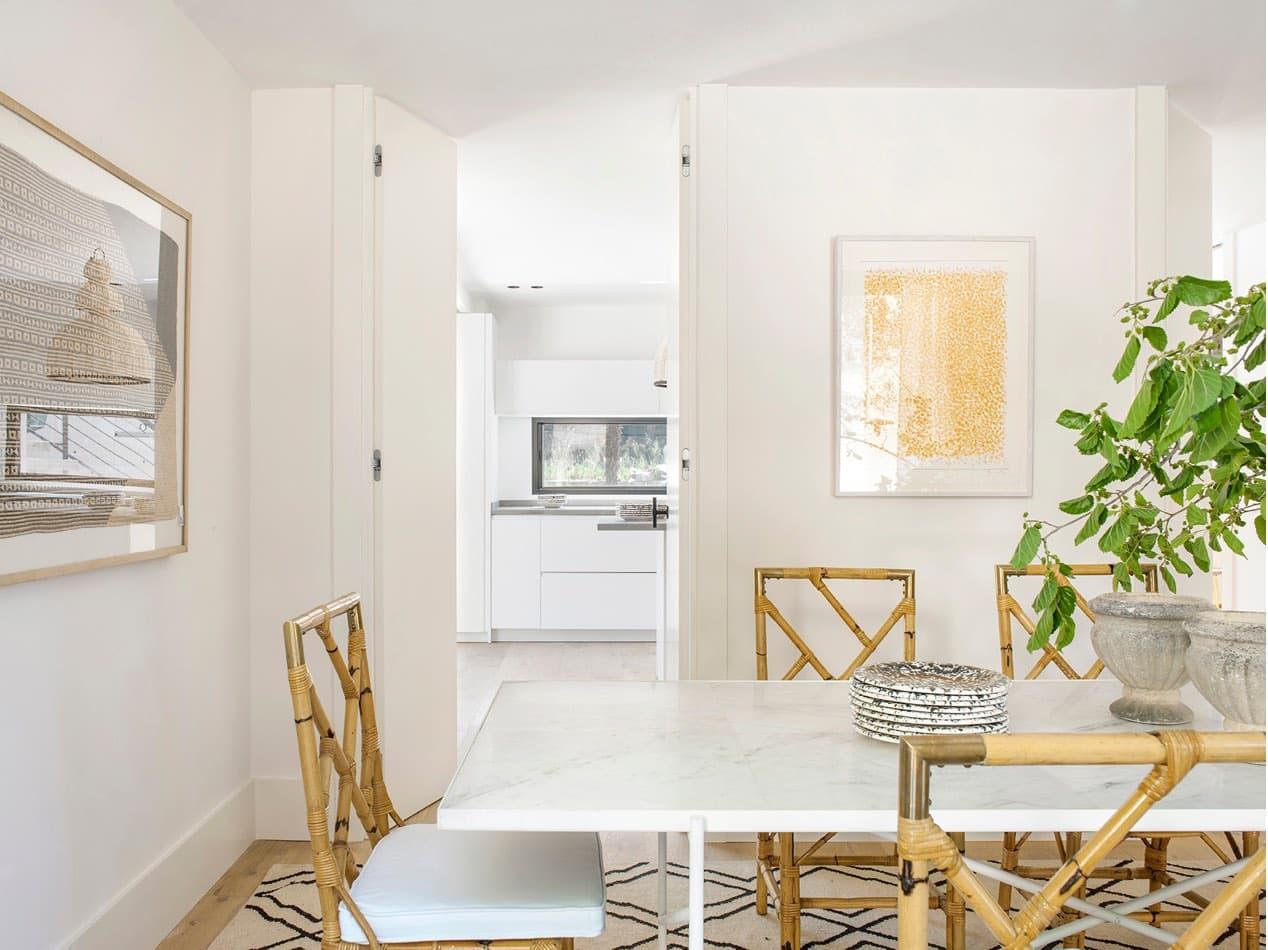Estudio María Santos Reforma integral y decoración de vivienda minimalista Madrid comedor con mesa blanca y silla de mimbre
