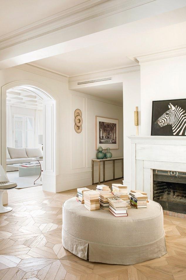 Estudio Maria Santos Reforma integral y decoración en Madrid salón minimalista en tonos blancos cuadro de cebra sobre chimenea puff de lino haciendo de mesa central con libros