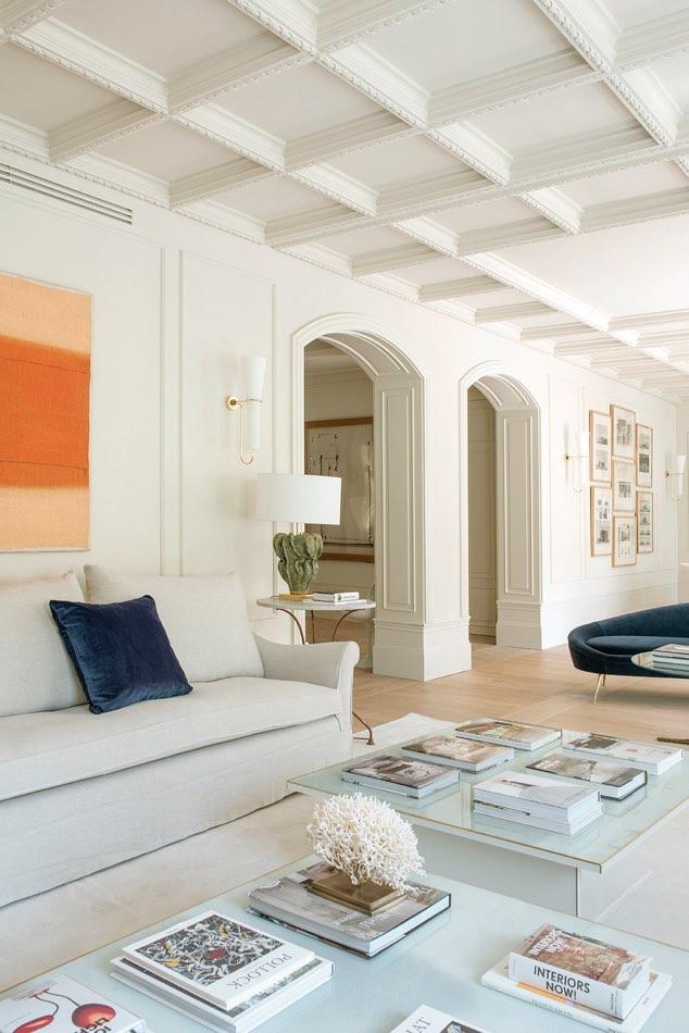 Estudio Maria Santos Reforma integral y decoración en Madrid salón minimalista en tonos blancos con sofá de diseño italiano de ico parisi de terciopelo azul